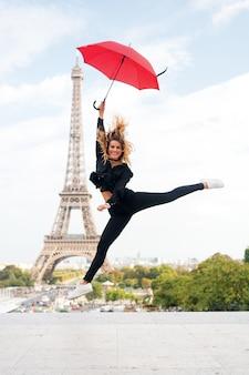 Dame met paraplu enthousiast over het bezoeken van de eiffeltoren, hemelachtergrond. dromen komen uit concept. lady toerist sportief en actief in het centrum van parijs springt op. meisjestoerist geniet van wandelen en sightseeing.