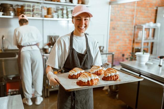Dame met pet houdt een dienblad met croissants versierd met verbrande room in de bakkerij