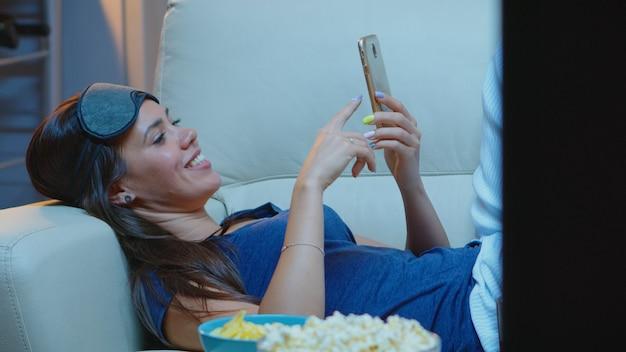 Dame met slaapmasker op voorhoofd en pijamas die op telefoon zoeken die in bank liggen. gelukkige vrouw zittend op de bank lezen, zoeken, browsen op smartphone via mobiel internet