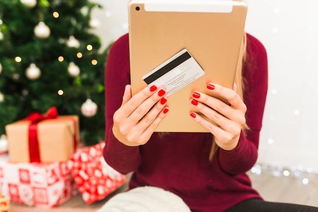 Dame met tablet en plastic kaart in de buurt van geschenkdozen en kerstboom