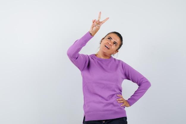 Dame met v-teken in wollen blouse en hoopvol