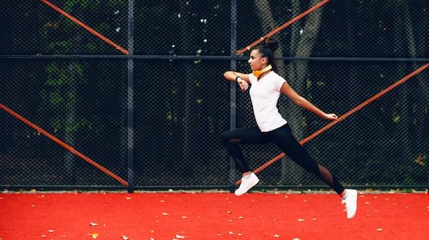 Dame met zwart haar en gele koptelefoon springt
