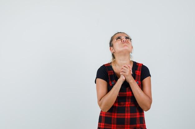 Dame omklemde handen in biddend gebaar in schortjurk en kijkt hoopvol, vooraanzicht.