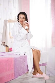 Dame ontspannen na massage zittend op bank in mooie salon