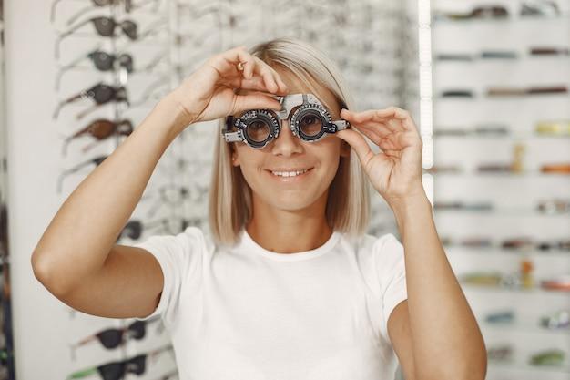 Dame oogtest en oogonderzoek. meisje met oogcontrole, met phoropter. vrouw in een wit t-shirt