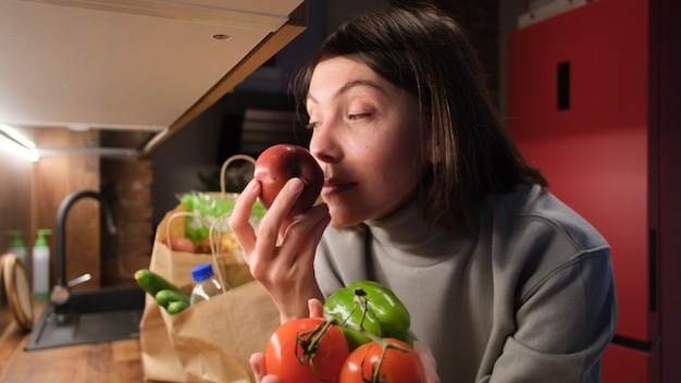 Dame ruikende tomaten en peper