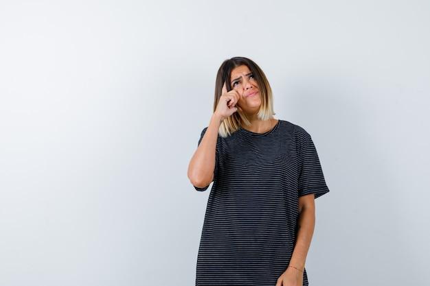 Dame staande in denken pose in zwart t-shirt en op zoek naar hoop. vooraanzicht.