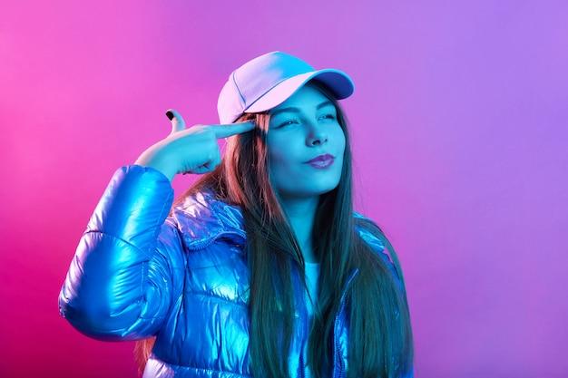 Dame tegen roze neon muur met denkbeeldige pistool in de buurt van tempel, schieten met vingers op haar hoofd