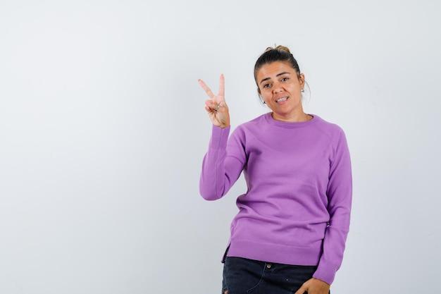 Dame toont v-teken in wollen blouse en ziet er zelfverzekerd uit