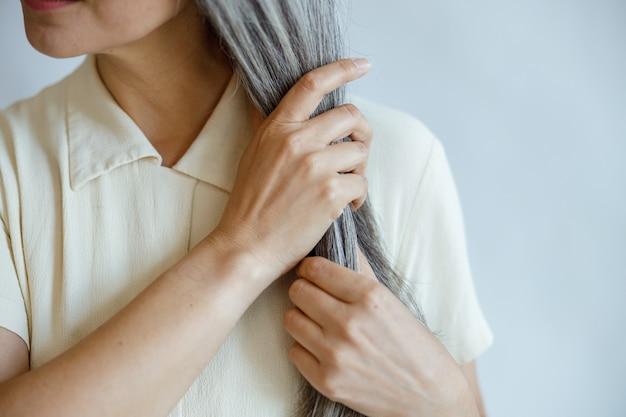 Dame van middelbare leeftijd in elegante blouse met rechte grijze haren poses op lichtgrijze achtergrond in studio close-up. volwassen schoonheid levensstijl