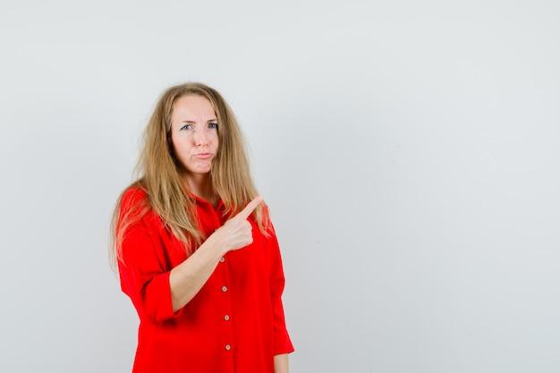 Dame wijst naar de rechterbovenhoek in een rood overhemd en kijkt twijfelachtig.
