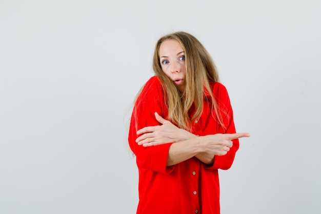Dame wijst naar de zijkant in rood shirt en kijkt verward,