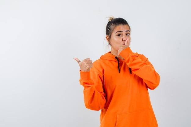 Dame wijst opzij met duim, toont stiltegebaar in oranje hoodie en ziet er verstandig uit Gratis Foto