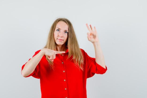 Dame wijst opzij, toont ok teken in rood overhemd en kijkt zelfverzekerd.