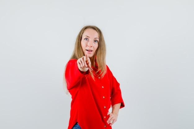 Dame wijzend op camera in rood shirt en kijkt verbaasd,