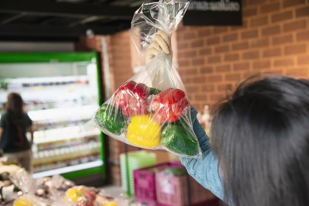Dame winkelt verse groente in supermarktopslag