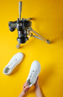 Dames beoordeelt nieuwe witte sneakers met camera op statief. bovenaanzicht. minimalisme Premium Foto