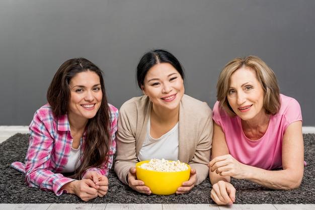 Dames die op vloer popcorn eten