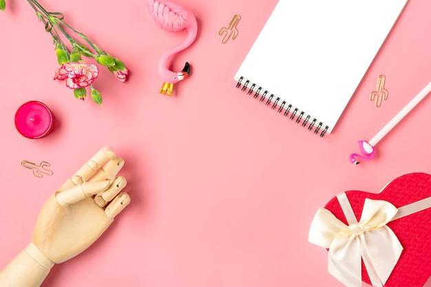 Dames dingen - notebook, flamingo, pen, anjer bloemen, houten hand, kaars, paperclips cactus, geschenkdoos hart op roze achtergrond