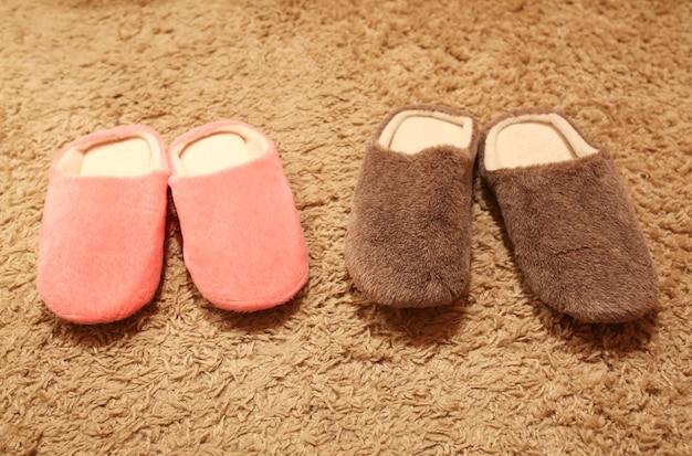 Dames- en herenpantoffels die op het tapijt staan. twee paar huisschoenen.