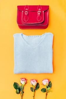 Dames garderobe. gebreid vest, rode tas. casual kleding op een geel