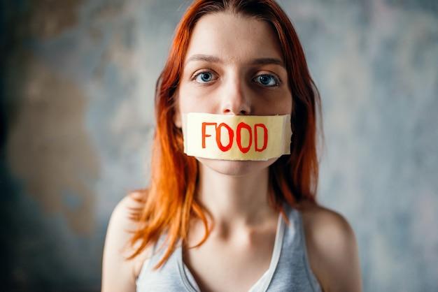 Dames gezicht, mond verzegeld met tape met label voedsel. vet of calorieën verbranden concept. gewichtsverlies, zware diëten, anorexia