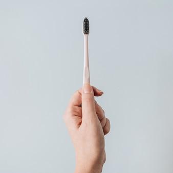 Dames hand houden tandenborstel op blauw. plat lag, bovenaanzicht mondverzorging, mondhygiëne concept