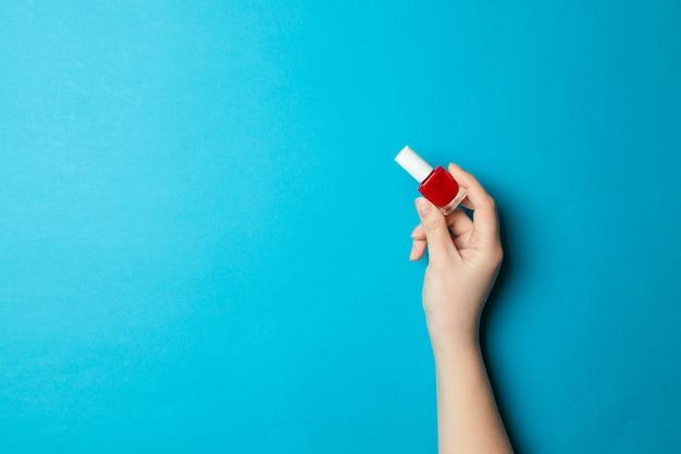 Dames hand houdt een glazen manicure een fles met rode vernis op een lichte donkerblauwe achtergrond.