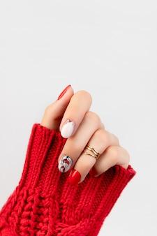Dames hand in trui met rode manicure op grijs