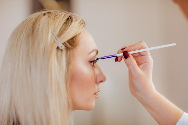 Dames hand make-up voor wimpers. blond vrouwenmodel. de nadruk ligt op het oog en de hand.