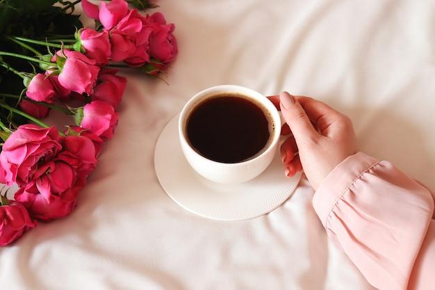 Dames hand met een kopje koffie in bed gezellige vakantie ochtend plat lag samenstelling met bloemen en kopje koffie vintage retro stijl