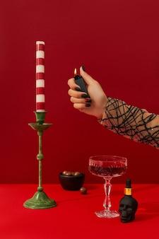 Dames hand met griezelig nagelontwerp zet de halloween-cocktail op tafel op rode achtergrond