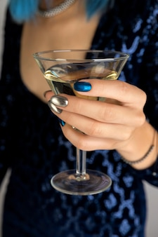 Dames hand met manicure met glas vermout achtergrond. partij donkere nacht zilveren spijkerontwerp.
