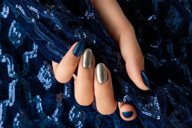 Dames hand met manicure op de creatieve blauwe sparkle achtergrond. partij donkere nacht zilveren spijkerontwerp.