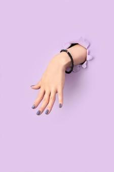 Dames hand met paarse matte manicure door gat in papier achtergrond. modieus lente-zomer nageldesign.