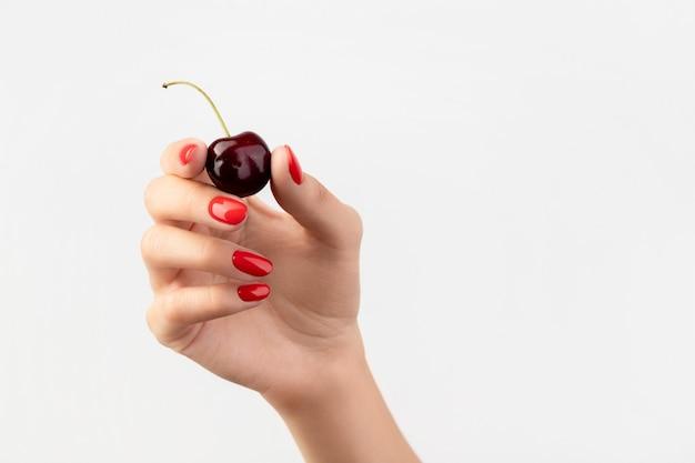 Dames hand met rode manicure bedrijf kers