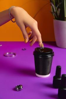 Dames hand met sieraden accessoires nagellak fles en papieren beker over paarse tafel
