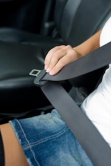 Dames hand met veiligheidsgordel in de auto - buitenshuis