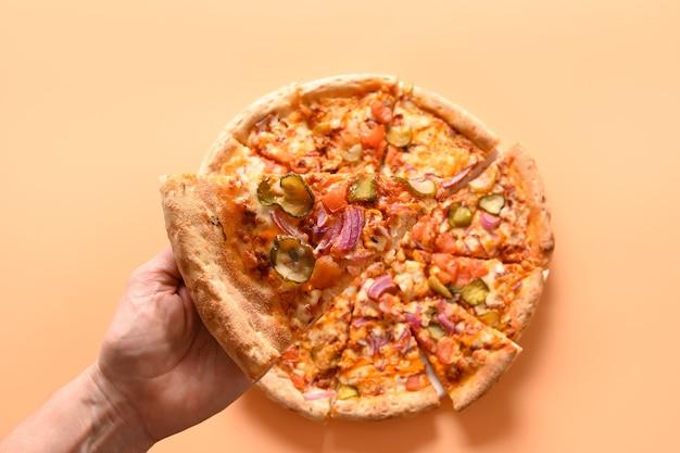 Dames hand nemen een verse italiaanse pizza met groenten.