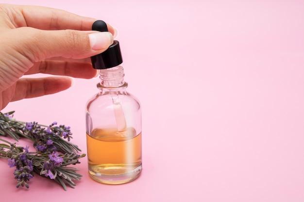 Dames hand trekt vloeistof in een pipet uit een glazen fles op een roze achtergrond met lavendelbloemen, kopie ruimte