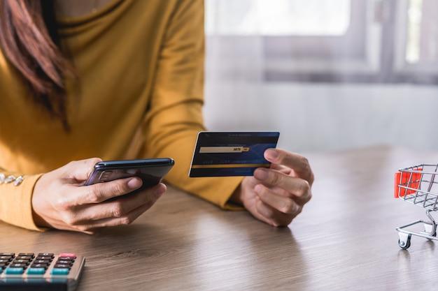 Dames handen in geel shirt met mobiele telefoon met leeg scherm en creditcard op kantoor en het gebruik van mobiele telefoon voor online winkelen, internetbankieren, online handelen