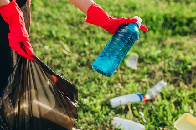 Dames handen in rode rubberen handschoenen. vrouw verzamelt afval in de zak. vrijwilliger spullen opruimen in het zomerpark. leuke vooruitstrevende vrouw die haar best doet om het milieu te helpen