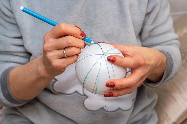 Dames handen maken van decoratie voor kerstboom.