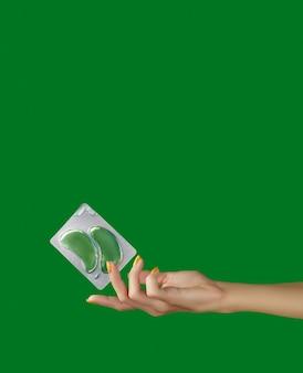 Dames handen met ooglapjes op groene achtergrondkleur