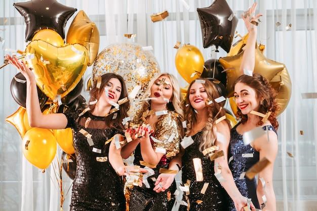 Dames in cocktailjurken gooien confetti, poseren voor een groot raam versierd met gouden ballonnen.