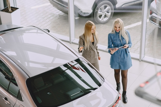 Dames in een autosalon. vrouw die de auto koopt. elegante vrouw in een blauwe jurk. manager helpt de klant.