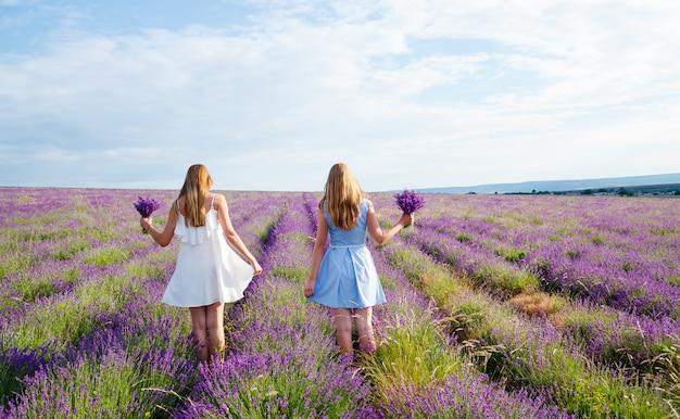 Dames in jurken die door een lavendelveld lopen