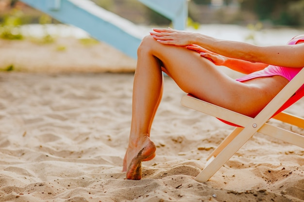 Dames lange slanke benen in roze bikini zittend op de stoel op het zandstrand