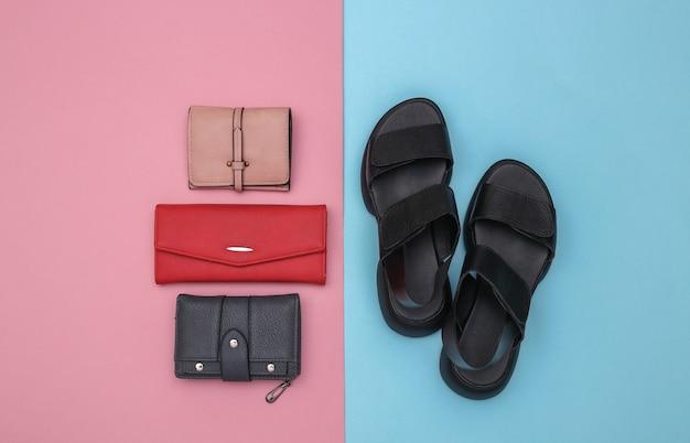 Dames lederen sandalen en portemonnees op roze blauwe achtergrond. accessoires voor dames. bovenaanzicht. plat leggen