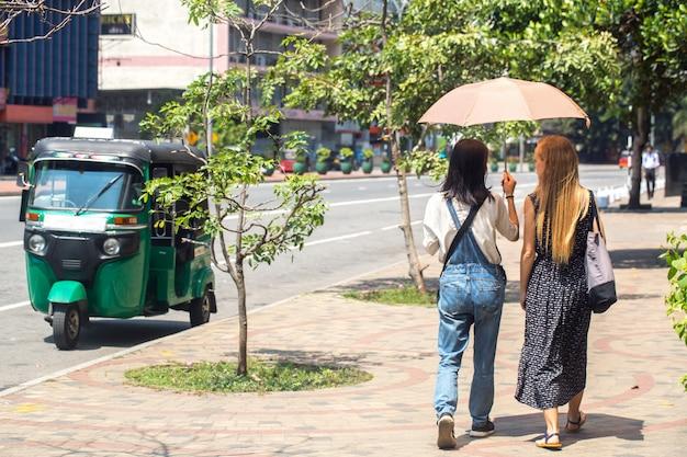 Dames lopen langs de weg